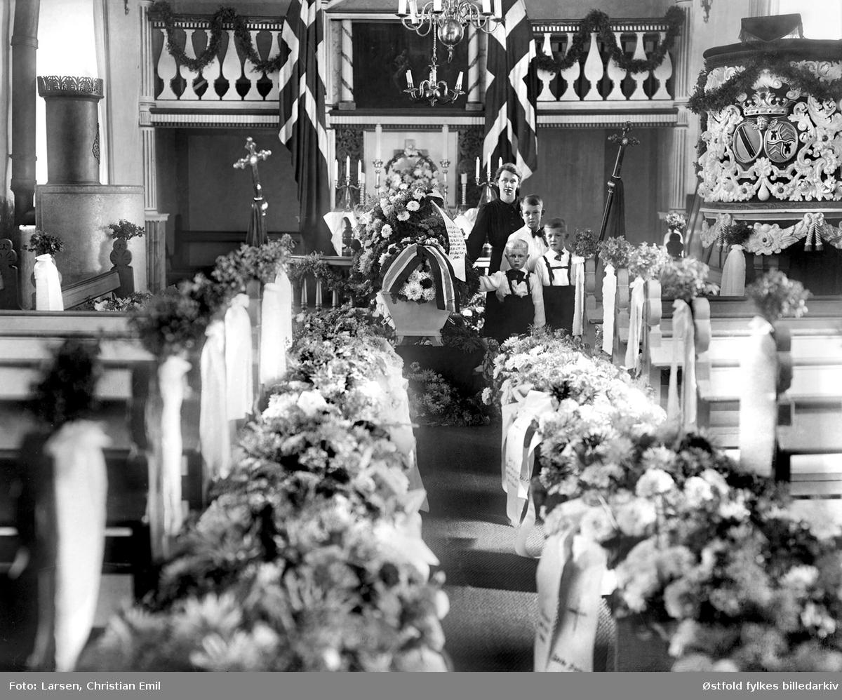 Begravelse i Ingedal kirke i Skjeberg i 1944. Begravelsen til gårdbruker Einar Molteberg f. 1906.  Ved kista står kona Augusta og deres tre sønner, Jens f. 1934 og Egil  f.1937 og Ivar f. 1939. De bodde på gården Øiestad søndre, i Skjeberg. Einar Ludvik Joachim Molteberg f. 1906, d. 1944, døde ved D/S Wesphalens forlis 8.september 1944.  50 norske politiske fanger ble sendt fra Norge til konsentrasjonsleir i Tyskland med troppe- og fangetransport-skipet D/S Westphalen. Skipet forliste 8.9. 1944 utenfor Marstrand i Sverige, og bare fem av de 50 norske fangene overlevde. Les på mer på Lokalhistoriewiki.no  På gravstøtta:   Død ved Westfalens forlis 8-9-1944  01  11  03  Alltid i kamp for Norges sak, selv bak gitter og lås du stred, inntil det redselens brak, trakk deg i bølgene ned