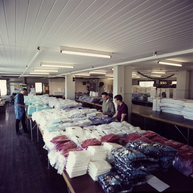 Tre arbeidere står ved en pakkedisk i manufaktur-engros-lageret til Jonas Øglænd Sandnes.