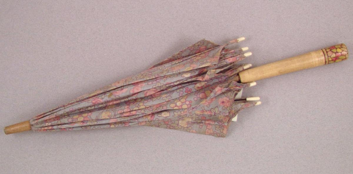 Ett parasoll, leksaks- av blommigt bomullstyg på trästativ försett med metallspröt. Tyget i färgerna blått, gult, grönt och rött. Längd ned en målad dekor i rött, gult och grönt. Har tillhört Kerstin Hellquist, givarens mor, som använde det på 1920-talet.