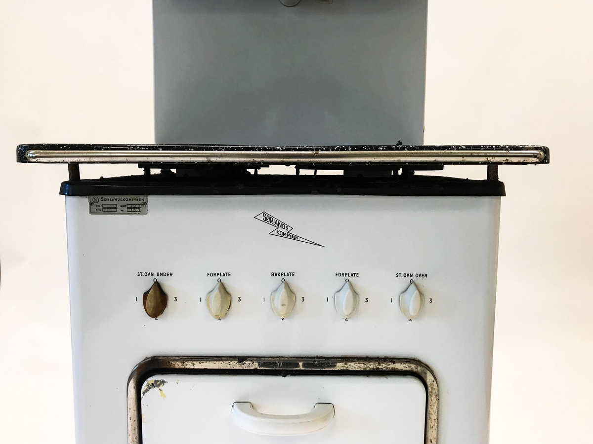 Elektrisk komfyr med bakvegg og tre kokeplater. Stekeovn med termometer på utsiden. I stekeovnen er det to tilhørende stekebrett. Lyspære på bakveggen.