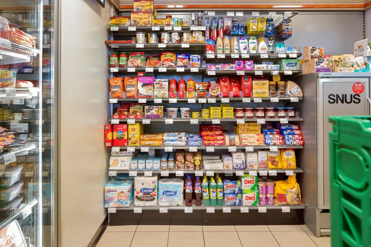 Statoil Dal. Butikk interiør med hylleseksjon med dagligvarer. Vaskemidler, hundefor, kjeks, toalettpapir og toalettartikler, ketsjup, syltetøy og matbokser. Et lukket skap med snus.