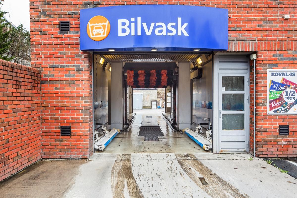 Statoil Nadderud. Åpen inngangsport til vaskehall med bilvaskemaskin. Skilt med Bilvask og reklameskilt på bygningens vegg.