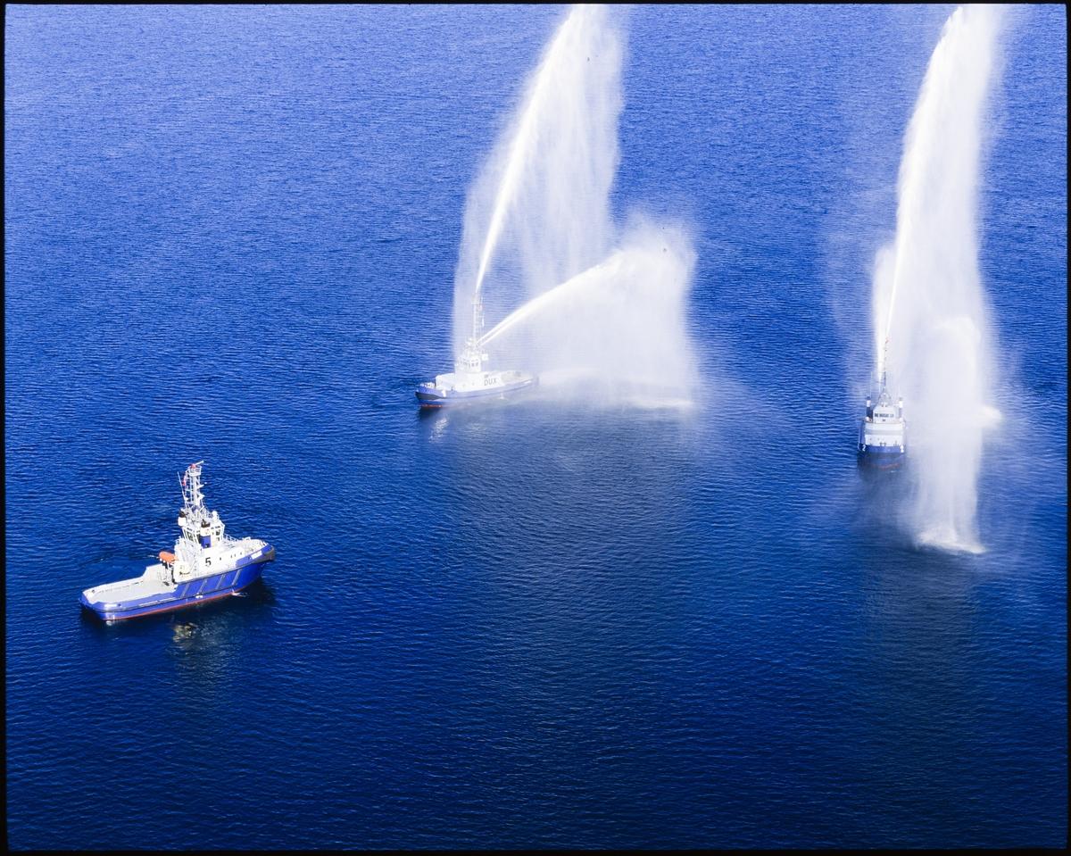 """Østensjøs taubåter """"Velox"""", """"Pax"""" og """"Dux"""" har en oppvisning hvor to av båtene spruter med vann for den tredje båten."""