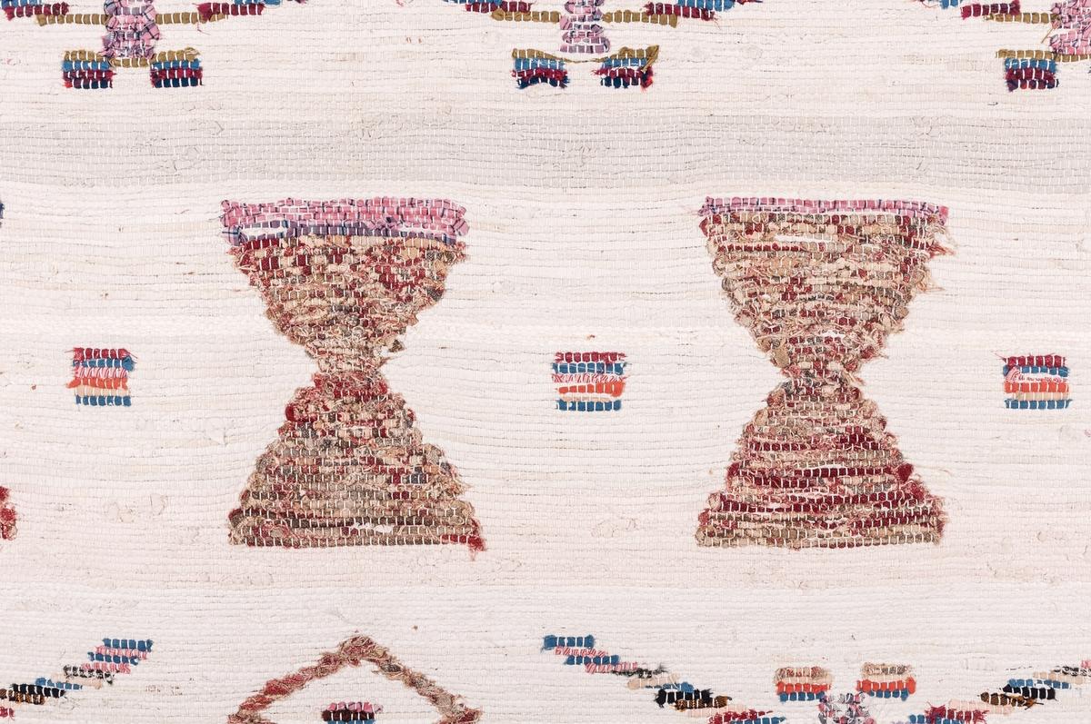 """Slarvtjäll, trasväv, (trastäcke, fäbodtäcke), 194 x 150. Kopia av gammalt slarvtjäll från Gästrikland. Varpen vitt bomullsgarn. Väften vita trasor. Mönstringen ej nockad utan inlagd. Insnodda svarta glesa bårder. I mönstringen ingå """"livsträd"""", """"timglas"""" och """"hjärtan"""".  Äldre katalogisering av Elisabeth Thorman (enl. uppgift)."""