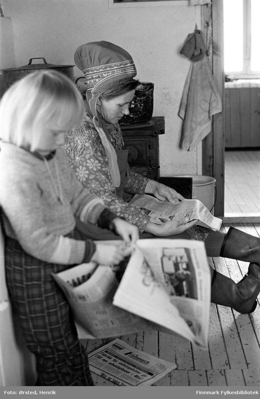 Anne Marie Isaksen Buljo og datteren Ragnhild Buljo, på kjøkkenet ved vinterbeiteplassen Bavdajohka.  I bakgrunnen ser vi en som leser avisen. Familien er fortsatt i Bávttajohka om vinteren.   Fotograf Henrik Ørsteds bilder er tatt langs den 30 mil lange postruta som strakk seg fra Mieronjavre poståpneri til Náhpolsáiva, videre til Bavtajohka, innover til øvre Anárjohka nasjonalpark som grenser til Finland – og ruta dekket nærmere 30 reindriftsenheter. Ørsted fulgte «Post-Mathis», Mathis Mathisen Buljo som dekket et imponerende område med omtrent 30.000 dyr og reingjetere som stadig var ute i terrenget og i forflytning. Dette var landets lengste postrute og postlevering under krevende vær- og føreforhold var beregnet til 2 dager. Bildene gir et unikt innblikk i samisk reindriftskultur på 1970-tallet. Fotograf Henrik Ørsted har donert ca. 1800 negativer og lysbilder til Finnmark Fylkesbibliotek i 2010.