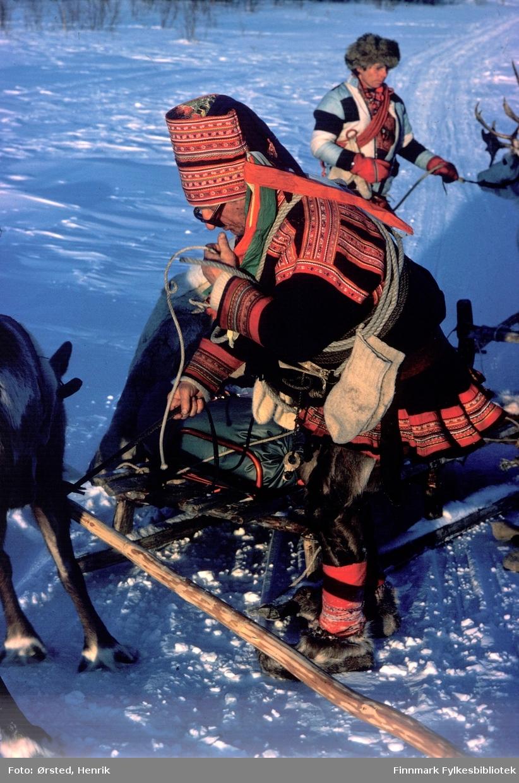 """Postfører Mathis Mathisen Buljo, bedre kjent som """"Post-Mathis"""" i samiske kretser, møter på reindriftssamer i arbeid på vidda. Her ser vi en same i kofte med lassoen på skrå over ryggen og vottene godt festet i lassoen. En kjørerein står klar mellom sledesjekene.   Fotograf Henrik Ørsteds bilder er tatt langs den 30 mil lange postruta som strakk seg fra Mieronjavre poståpneri til Náhpolsáiva, videre til Bavtajohka, innover til øvre Anárjohka nasjonalpark som grenser til Finland – og ruta dekket nærmere 30 reindriftsenheter. Ørsted fulgte «Post-Mathis», Mathis Mathisen Buljo som dekket et imponerende område med omtrent 30.000 dyr og reingjetere som stadig var ute i terrenget og i forflytning. Dette var landets lengste postrute og postlevering under krevende vær- og føreforhold var beregnet til 2 dager. Bildene gir et unikt innblikk i samisk reindriftskultur på 1970-tallet. Fotograf Henrik Ørsted har donert ca. 1800 negativer og lysbilder til Finnmark Fylkesbibliotek i 2010."""