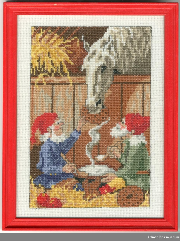 Två tomtar sitter på golvet i ett stall. De äter gröt ur ett stort grötfat. Bredvid dem på golvet ligger två äpplen och ett knäckebröd. En vit häst blir matad med bröd av den ene tomten.