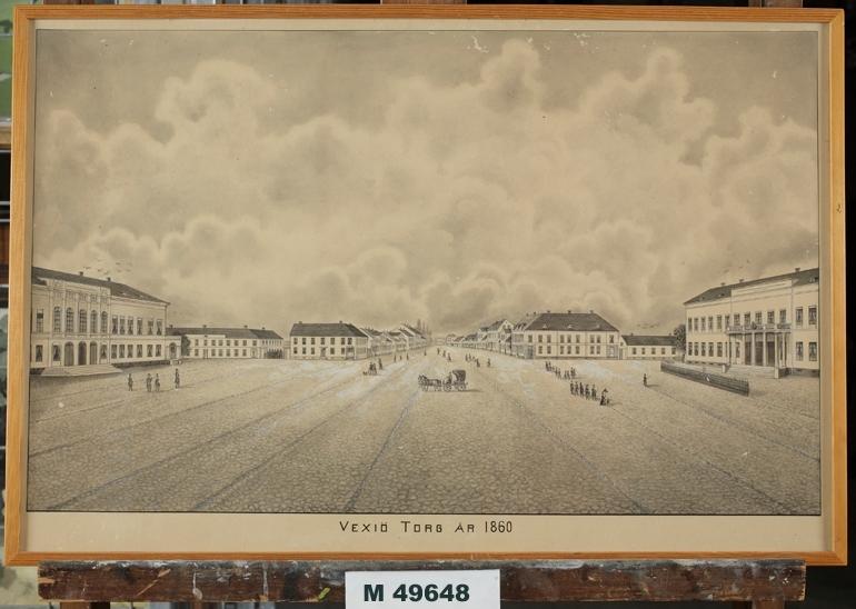 Litografi. Stor litografi föreställande Växjö torg (Stortorget) år 1860, mot väster. Till vänster syns Stadshotellet och till höger Residenset. Verkar delvis ha varit färglagd (handkolorerad) från början.