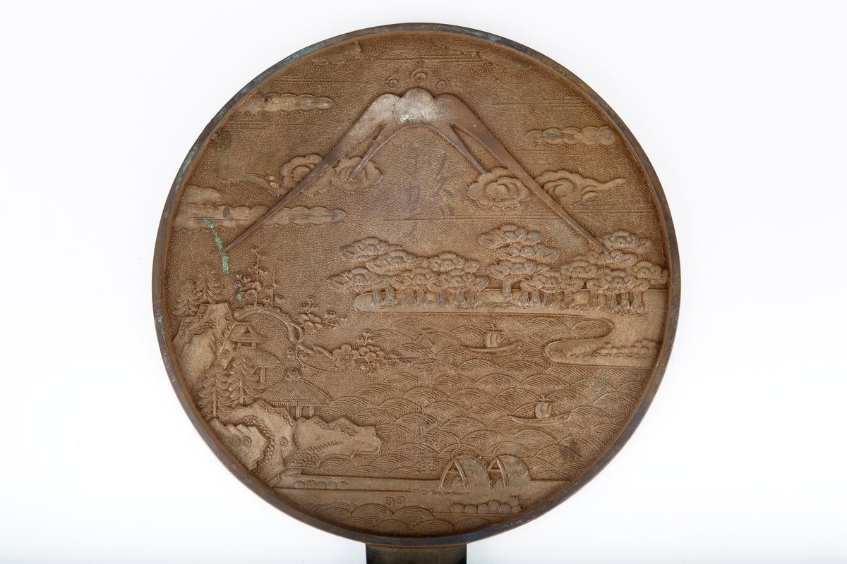 """Sirkelrund metallplate med skaft. Relieff med motiv fra Østen. Også noen japanske(?) bokstaver. Skaftet er """"isolert"""" med en slags strå. Derfor kan gjenstanden også tolkes som f. eks. en bordskåner. Kan dt være sølv?"""