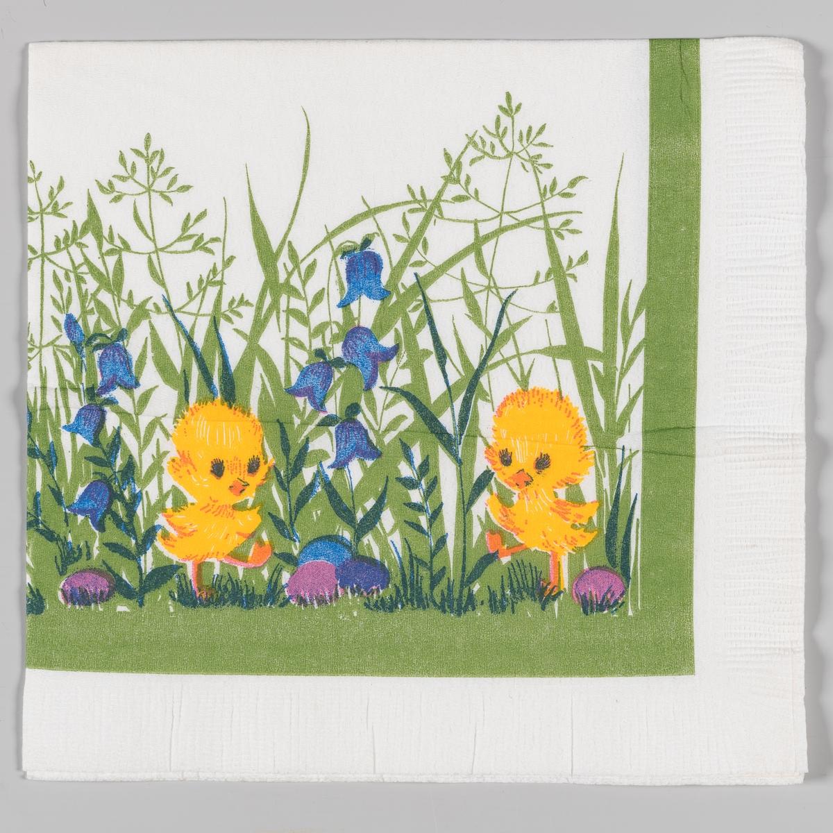 To kylling står mellom høyt gress med klokkeblomster og kulørte påskeegg. Grønn kantstripe.