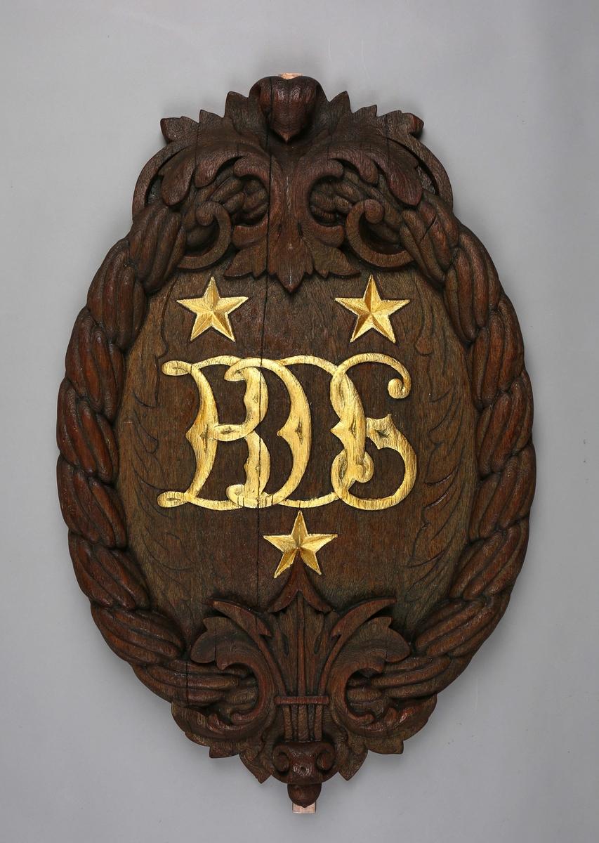 Emblem dekort med tau og bokstavene BDS utskårtet i tre.