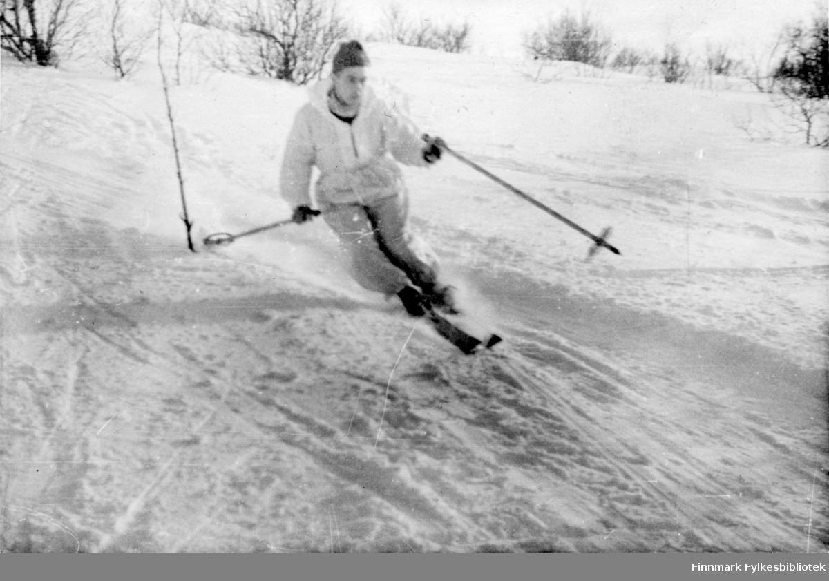 """Soldat fra 2.Bergkompani i hvit anorakk og skibukser på ski i Finnmark. Arne Arnesen forteller: """"Like over jul begynte kompaniet å trekke over fjellet til Børselv i Porsangerfjorden. Vi gikk i puljer. I min pulge var vi 18 mann. Der opplevde jeg, og sikkert de øvrige også, den sterkeste snøstorm vi noen gang hadde sett maken til. Vi organiserte oss etter beste evne før uværet slapp til for alvor. Avstanden måtte være minimal, det var ikke sikt på mer enn en meter eller to. Jeg plasserte de sterkeste bak, å gi opp var ikke tillatt. En hvit samojedhund husker jeg, den holdt seg ved siden av meg i stormen. Hvor den kom fra, vet jeg ikke, den hørte vel ikke hjemme noe sted stakkar. Plutselig blåste den rett og slett utfor en skråning, men den kom til oss igjen noen dager senere.""""   Bildeserien """"Frigjøringen av Finnmark 1944-45"""" viser et unikt materiale fotografert av soldater i Den Norske Brigade, 2. Bergkompani under deres oppdrag """"Frigjøringen av Finnmark"""" som kom i stand under dekknavn """"Øvelse Crofter"""". Fakta rundt dette bildematerialet illustrerer iflg. vår informant, George Bratli: """"2.Bergkompani, tilhørende Den Norske Brigade i Skottland,  reiste fra Skottland 30. oktober 1944 med krysseren «Berwick» til Scapa Flow på Orkenøyene for å slutte seg til en større konvoi som skulle være med til Norge. Om bord på andre skip var det mange russiske krigsfanger som hadde vært på tysk side og som nå ble sendt hjem.  2.Bergkompani forlot havn 1.november 1944 og kom til Murmansk, Sovjetunionen, 6. november 1944.  De ble her lastet om og fraktet til Petsamo, Sovjetunionen, hvor de ankommer 11.november 1944.  Kompaniet reiser så til Sandnes utenfor Kirkenes og blir forlagt der frem til 26.november 1944. De flytter så videre til Skipparggura.  Den 29.november reiser deler an kompaniet til Rustefielbma og Smalfjord og noen drar opp på Ifjordfjellet.   17. desember ankommer resten av kompaniet til Smalfjord. 30.desember blir en avdeling sendt til Hopseide og 8. januar 1945 blir no"""