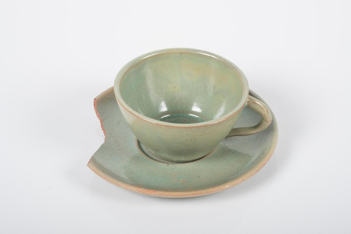Kopp med skål i keramikk med grønn lasur. Buet hank på koppen. Koppen og skålen har spor etter tre knotter på bunnen, usikker funksjon. Bunnen på skålen har matt overflate. En brukket del av skålen mangler.