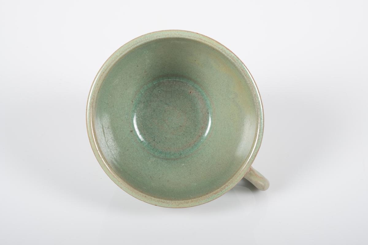 Kopp i keramikk med grønn lasur. Buet hank. Spor etter tre knotter på bunnen, usikker funksjon.