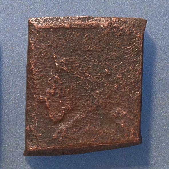 1 öre Fyrkantigt mynt. Åtsidan: tre kronor placerade i V-form, svagt skönjbara. Versalen R till höger om kronorna. Det fyrsiffriga präglingsåret - längst ner på myntet - är oläsligt. Ocentrerad prägling. Ram delvis synlig. Frånsidan: två korsade pilar under en krona, svagt skönjbara. Till vänster om pilarna siffran 1, till höger versalerna ÖR, svagt skönjbara. Ocentrerad prägling. Ram delvis synlig. Nuvarande skick: bägge sidor slitna. Vikt: 25,1 gram.  Text in English: Square-shaped coin. Denomination: 1 öre. The obverse side has three crowns spaced in a V-shape, partly visible. The initial R is placed to the left of the crowns. The four digit year of coinage, is not legible. The coin stamp is off-centre. The frame is partly visible. The reverse side has two crossed arrows beneath a crown, faintly visible. To the left of the arrows is the numeral 1, to the right the initials ÖR, faintly visible. The coin stamp is off-centre. The frame is partly visible. Present condition: both sides are worn. Weight: 25,1 gram.