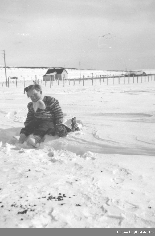 """""""Solveig. En pust i bakken."""" Familiealbum tilhørende familien Klemetsen. Utlånt av Trygve Klemetsen. Periode: 1930-1960. Bildet viser Solveig Klemetsen fotografert sittende i snøen med Fanamønstret genser og skjerf i halsen. I bakgrunnen sees veien, et gjerde og et par spredte uthus."""