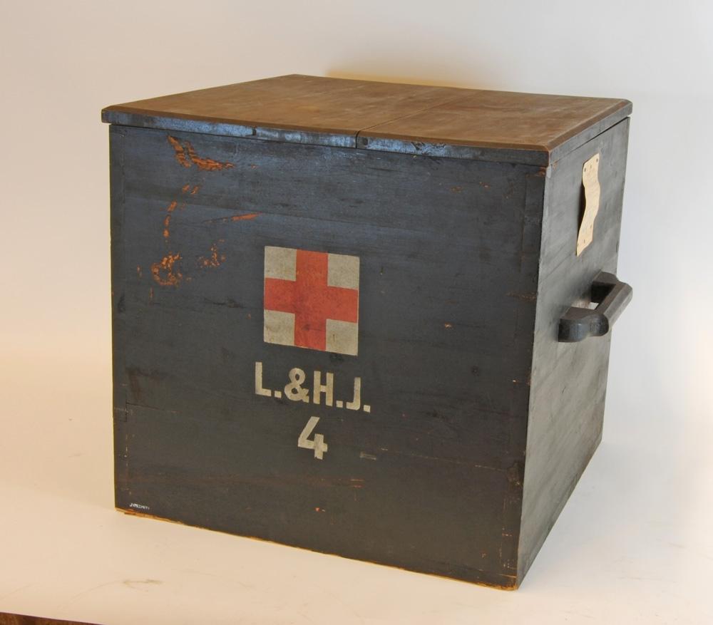 """Låda av trä, målad svart, med rött kors med vit bakgrund på fram och baksidan. Under korset är den märkt """"L.&H.J. 4"""". Brunmålad inuti. På sidorna sitter bärhandtag. Tillhörande lock (se Jvm 20467:2)."""