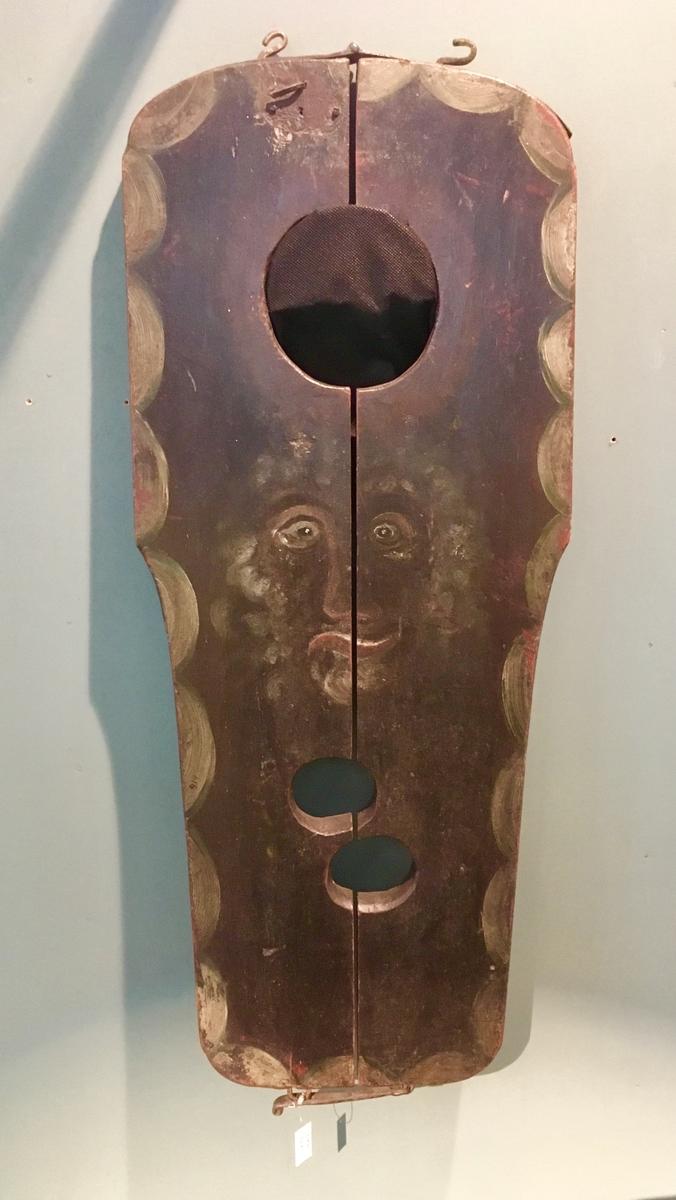 Treplate som kan tas fra hverandre i to deler med to hull for håndledd og et større hull for hals. Malt i en mørk farge og påmalt et ansikt med oppsperrede øyne. Påmalt dekor rundt kanten.