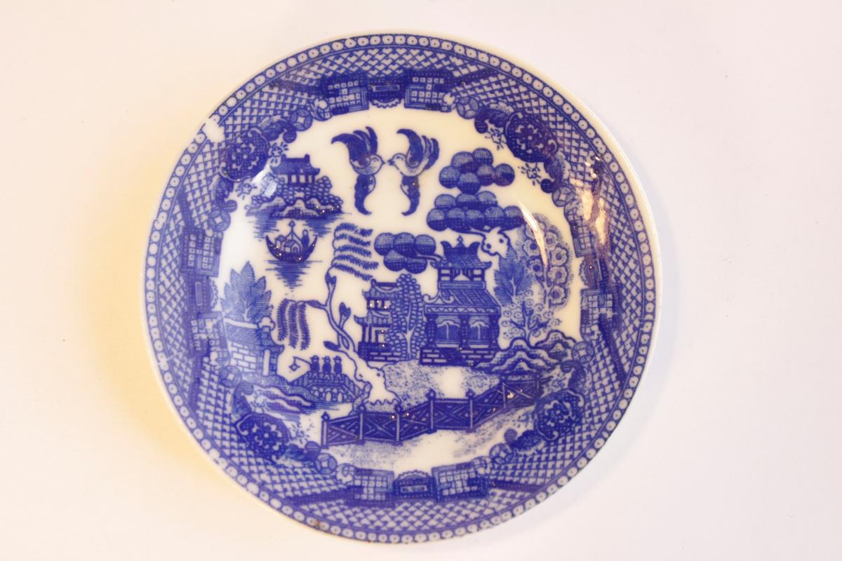 Blåvit mattallrik med kinesiskt landskap, pagoder, träd och fåglar. Tillhör dockservis