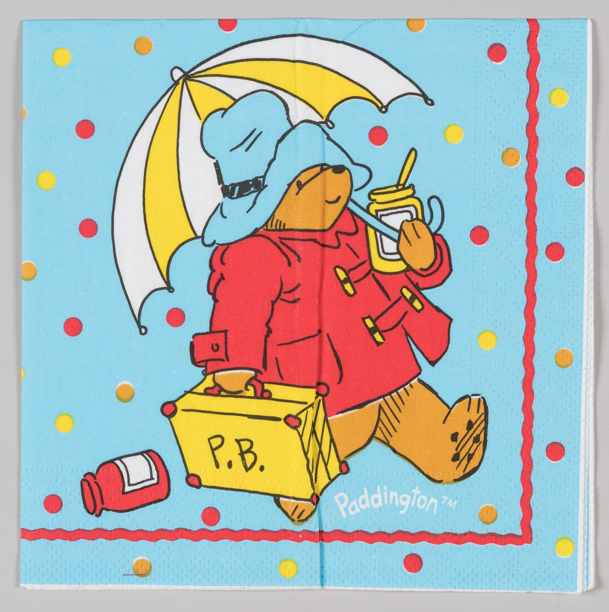 Bjørnen Paddington med frakk, hatt, paraply og koffert.  Bjørnen Paddington er hovedperson i en rekke barnebøker av forfatteren Michael Bond som utkom fra 1958.