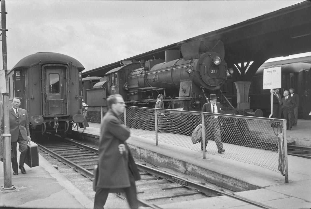 Tog og reisende på Trondheim stasjon. Damplokomotiv type 30b nr. 359.