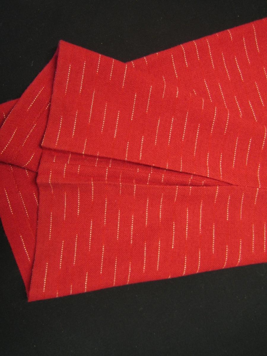 """Dräkt med kjol och jacka i röd ull med ränder i flamgarn. Tyget är vävt med entrådigt ullgarn i både varp och inslag. Jackan är dubbelknäppt i rak modell med rakt isydda ärmar med kil. och två fickor på framstyckena. Jackan knäpps med tio tryckknappar i grå metall. Halsen är rundringad med en stickad krage. Ärmarna avslutas med en 19 cm lång mudd. Kjolen är av rak modell med sidsömmar och ett  gångveck 29 cm långt i vänster sida, 3 cm bred linning i vänster sida. En lapp är fastsatt på jackan med texten """"UTMÄRKT SVENSK FORM"""" på ena sida och """"jacka Flam ylle tygbredd 125 cm, PRIS: 375:-/m, formgivare: A-M Nilsson beställningsvara (jacka modell)"""" på andra sidan."""