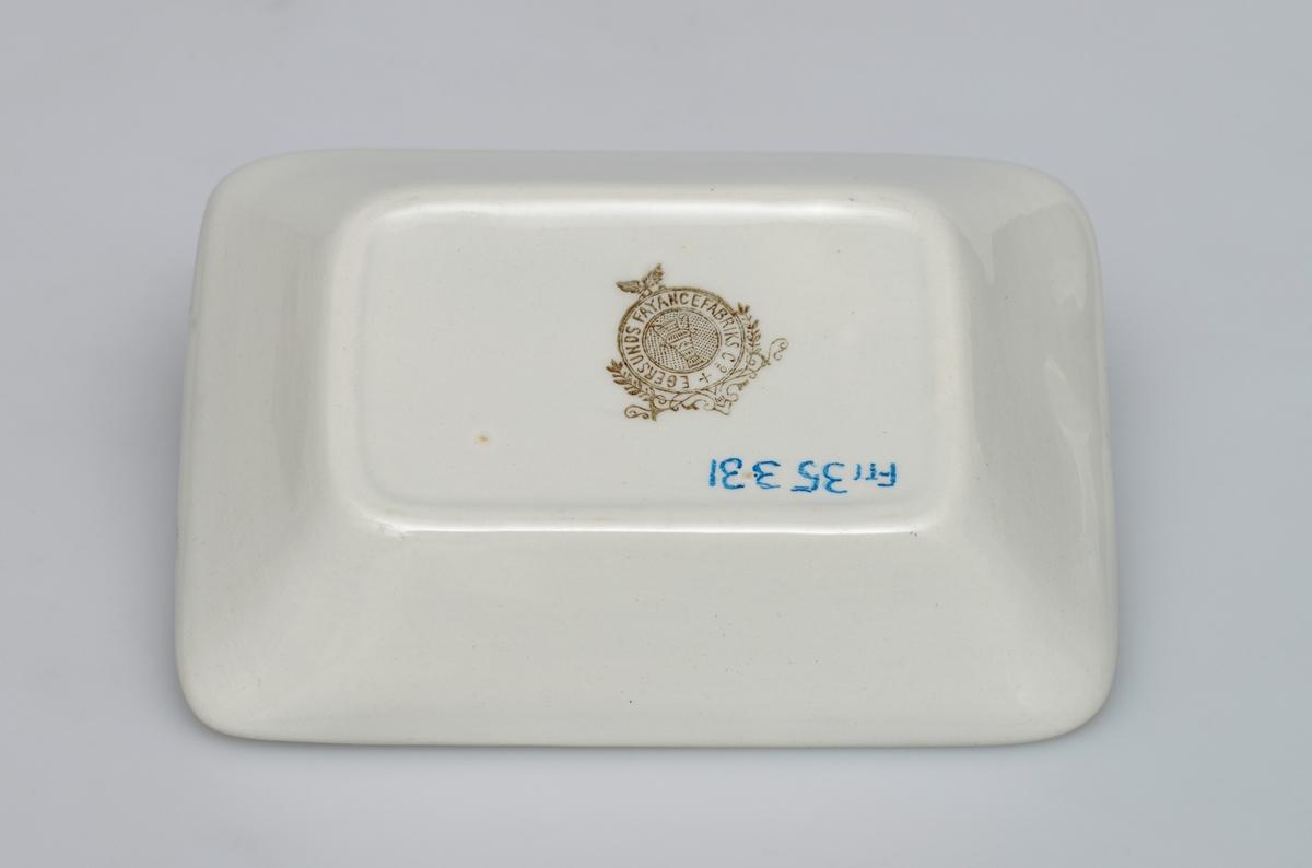 """Består av vaskefat, vannmugge, 2 såpekopper. To såpekopper laget av keramikk. De har lik utforming og dekor, men har ulik størrelse. Såpekoppene er rektangulær med avrundede hjørner. Koppen er laget slik at det er """"rominndeling"""" i bunnen (tre rom). Langs kanten er det gulldekor som er delvis slitt bort. På undersiden er det stempel med tekst og bilde, se """"Påført tekst/merker""""."""