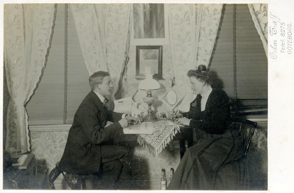 Interiör, Oskar och Mariana Träff sitter vid ett litet bord placerat mellan två fönster. Mariana till vänster skriver och Oskar har en tidning på bordet framför sig. Han verkar säga något till Mariana. På bordet står skrivdon och en fotogenlampa. På golvet under bordet står två flaskor.