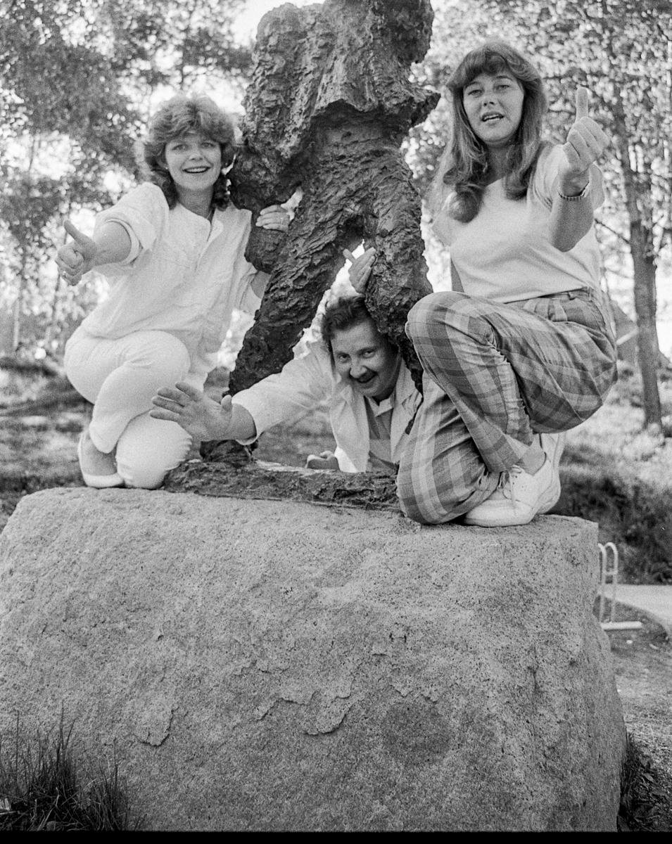 Medlemmene i arrangementkomiteen for Langhusdagene. To damer og en mann sitter på en stor sten med en bronsefigur mellom seg.