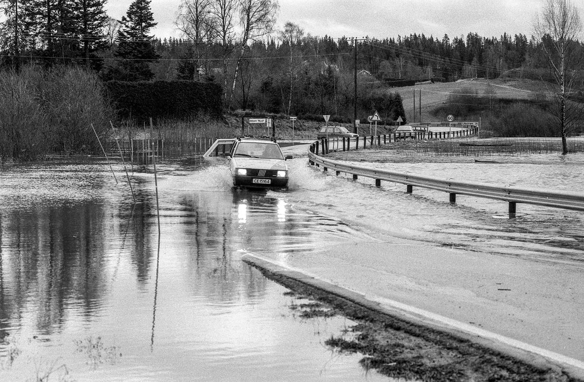 Flom i Enebakk over veier og jorder, biler kjører i flomvannet.