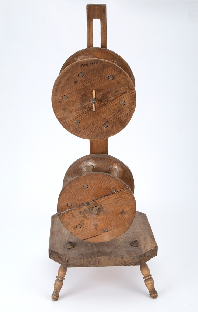 Håndlaget. To tromler på en trepinne, montert på en plate med fire ben.