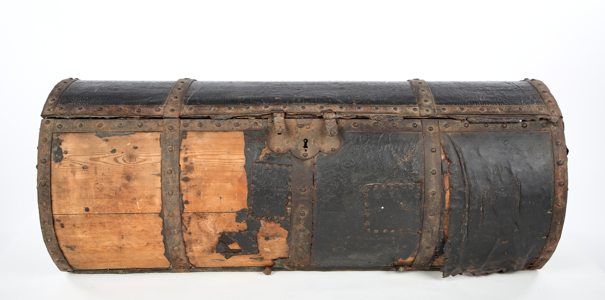Rund og avlang lærtrukket reisekoffert. To bærehåndtak og beslag av smijern. Lås med tre nøkkelhull. Innvendig tapetsert med blått og hvitt rosemønstret papir.