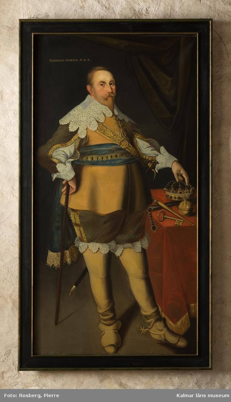 Gustav II Adolf i helfigur, stående i  halvprofil åt höger. Porträtterad i gult kyller, blå fältbindel, jacka under kyllret med uppsplitsade ärmar, skjorta med stor spetskrage och stora spetsmanschetter. Guldbroderat värjgehäng med stor värja. Byxor nedstoppade i de uppdragna ridstävlarna. Ur stövlarna sticker en spets fram.