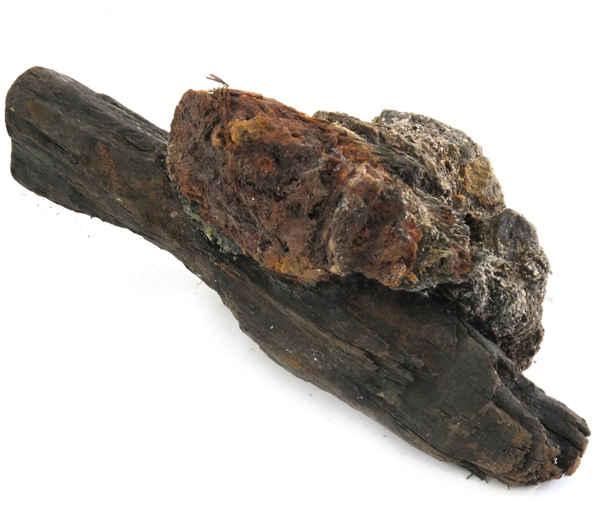 Korrosjonklump g)  Korrosjonsklump med et stykke fargetre. Består ellers av jern, rust, stein, sand og uidentifisert materiale.