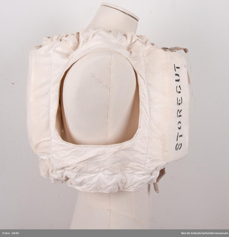 Redningsvest i seilduk og kork. Mellom fire poser med kork er det hull til armer. Knytes i front med lisser i tekstil
