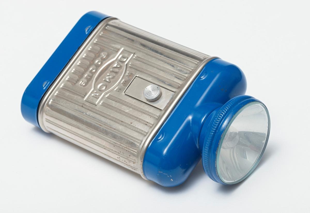Lommelykt i metall, drevet av et 4, 5 volts batteri (3LR12), som settes inn via ei luke i bunnen. Lykta er rektangulær i formen med avrundete kanter som gir et ovalt tverrsnitt, påfestet en traktformet del med pære og klart, rundt glass i toppen. Lykta er delt i tre felter, der midtpartiet har er mønster av langsgående riller i metallfarge. De andre partiene er lakkert i blått. En metallskrue over modellnavnet.