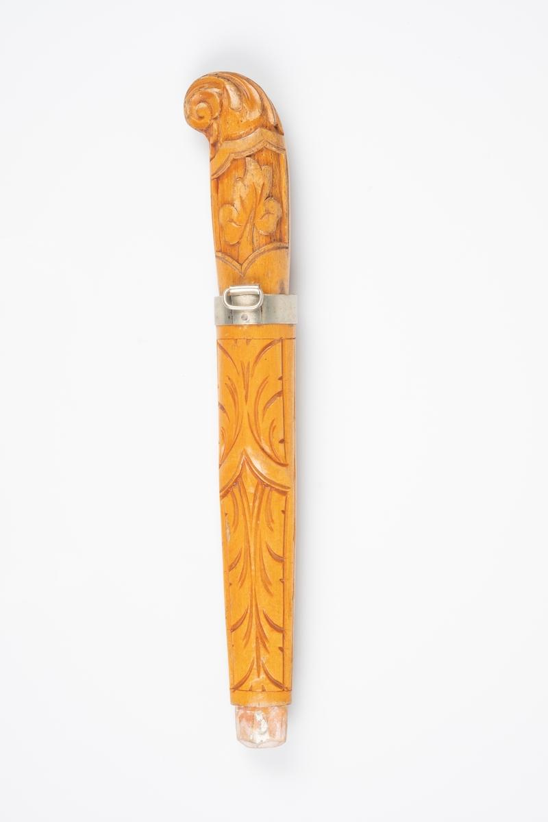 Skaft og slire av tre. Knivbladet mangler. Skaften og sliren er utsmykket med utskjæringer av akantus. Sliren har en metallkant med oppheng. Det ser ut som spissenden har hatt beslag av metall. Det er initialer som er svakt inngravert på skaftet. Enden/hodet på kniven er rund og buet.