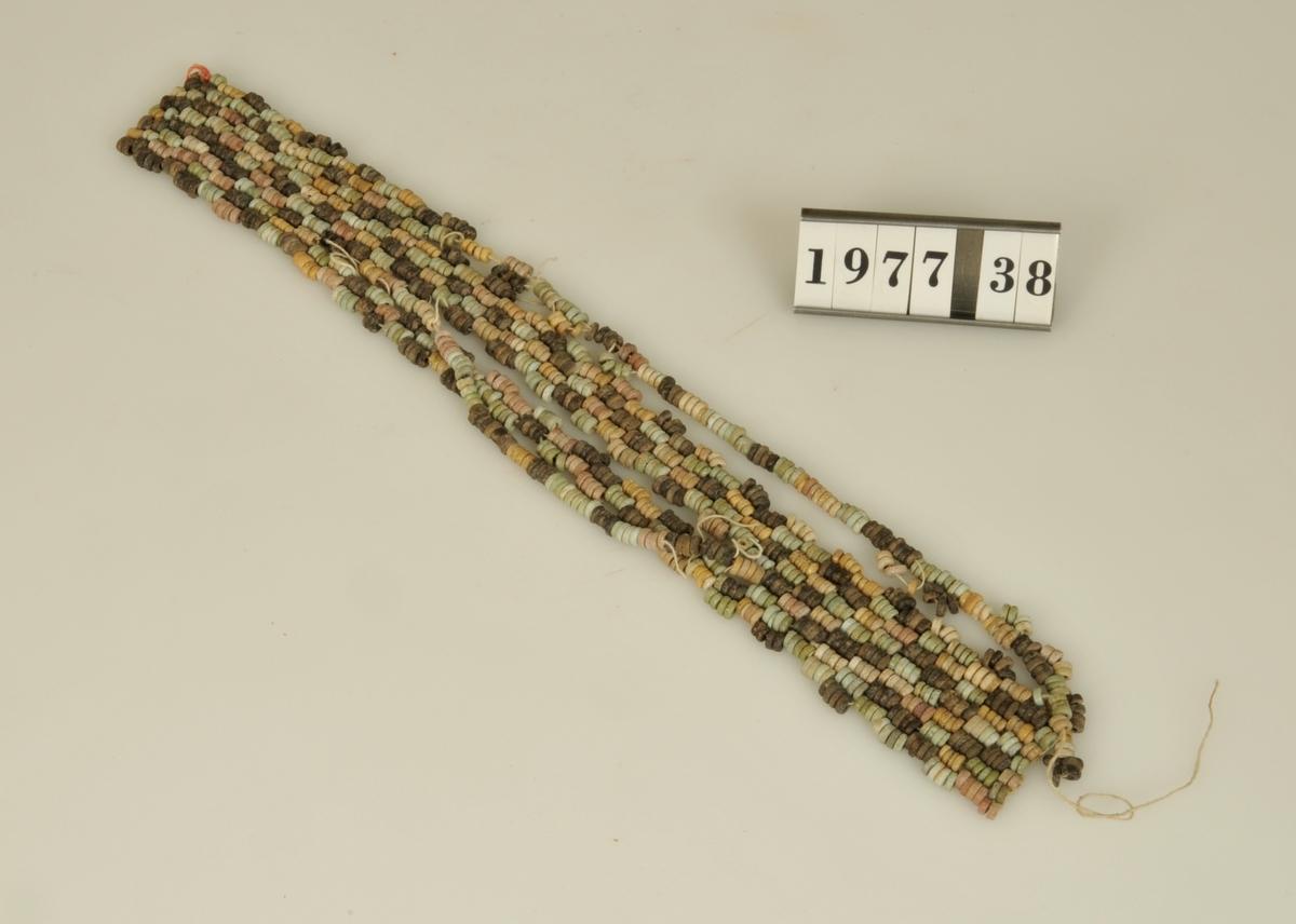 Halsband av små fajanspärlor i olika färger. Defekt.