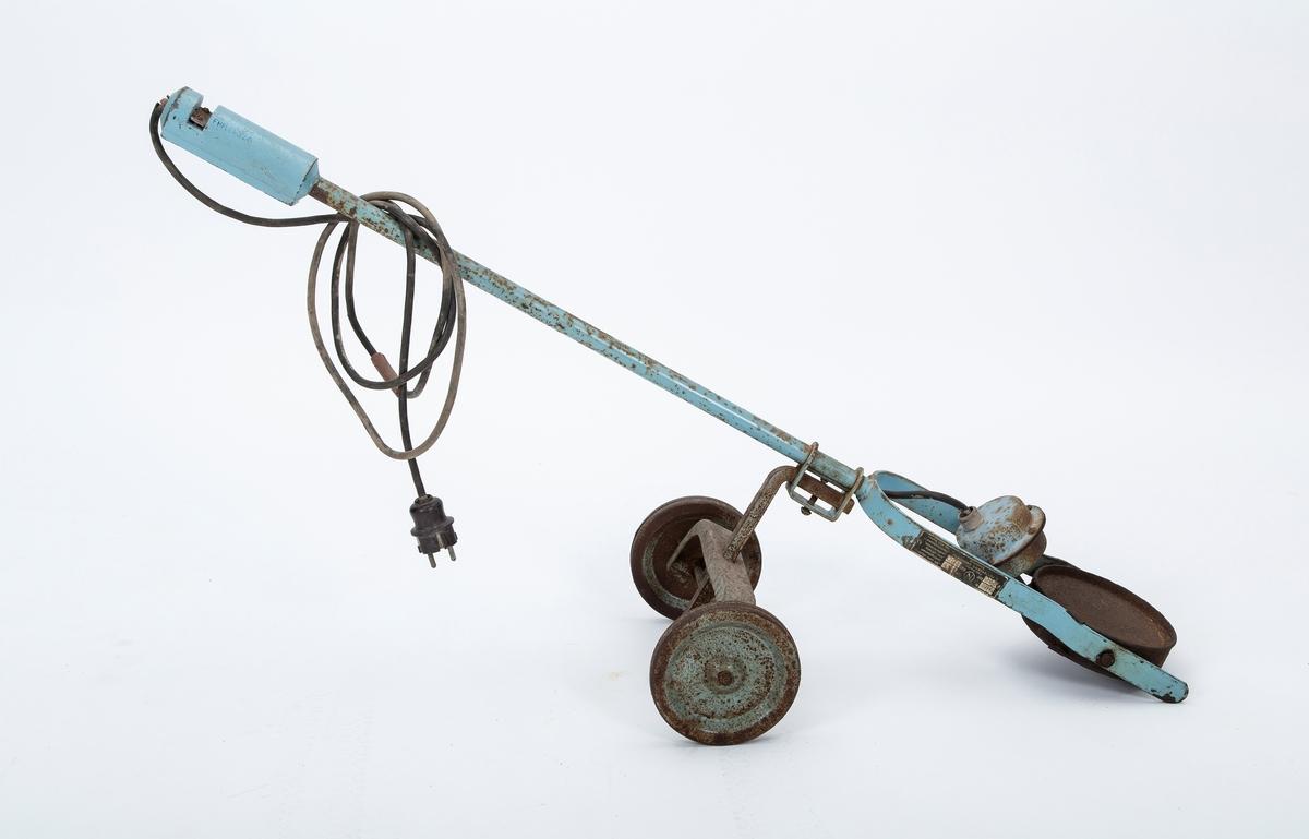 Elektrisk motorvarmer til bil. En rund varmeplate på to hjul. Tilkobles strøm og plasseres under bilmotoren ved hjelp av et håndtak. Industrielt fremstilt eller fra bygdesmie.