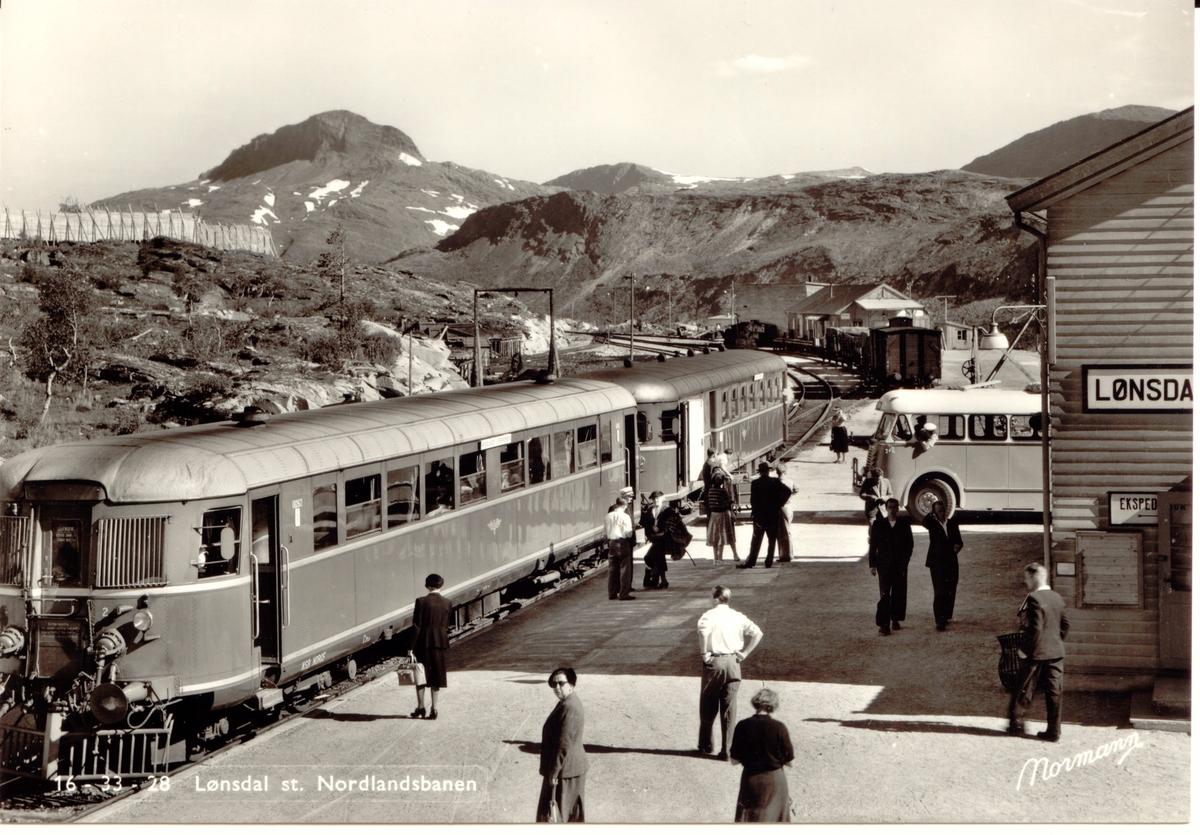 """Lønsdal stasjon med reisende fra """"Nordlandsekspressen"""" og ventende buss. Dieselmotorvogn type 6 nr. 18262."""