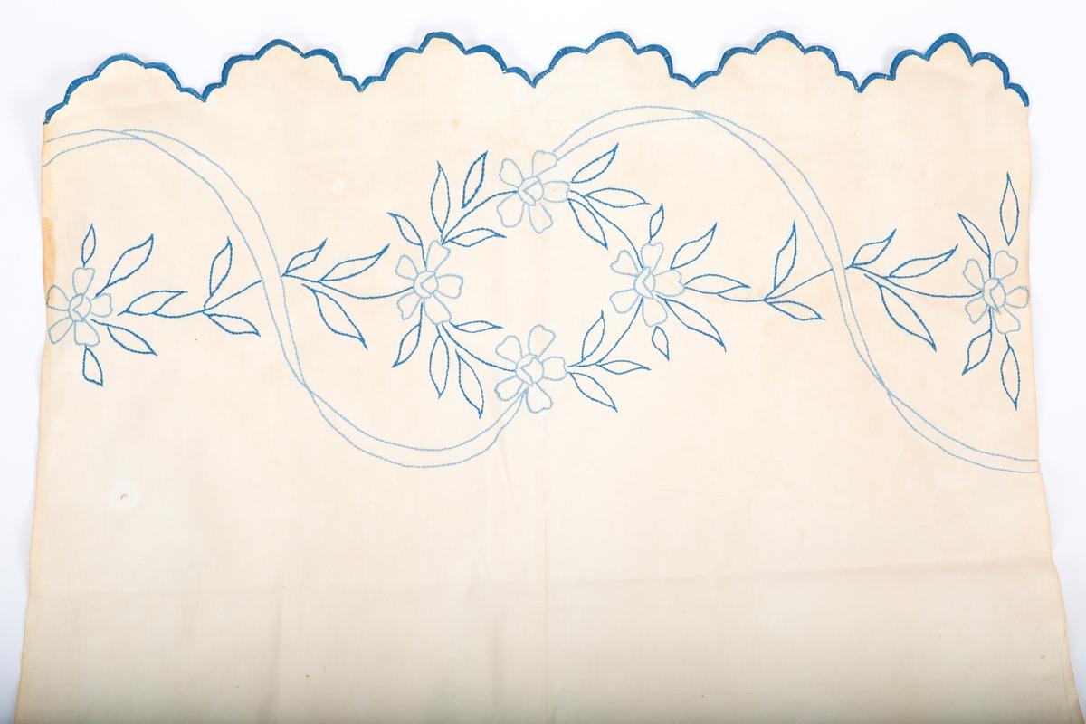 Vevet med blått konturstingsbroderi. Motiv; Blomster og ranker- Blåbroderte tunger i hver ende. Fabrikkert