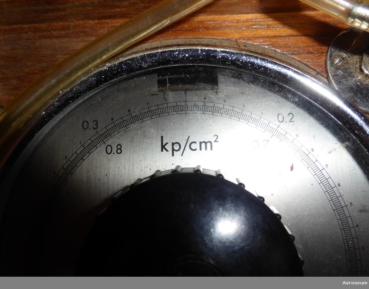 En precisionsmanometer i lackat trähölje, tillverkad av L M Ericsson, med manometer från System Paulin. I lådan sitter en display med en vridbar ratt och nålvisare och en genomskilig slang som sitter fast i ena enden med en metallbit i andra.