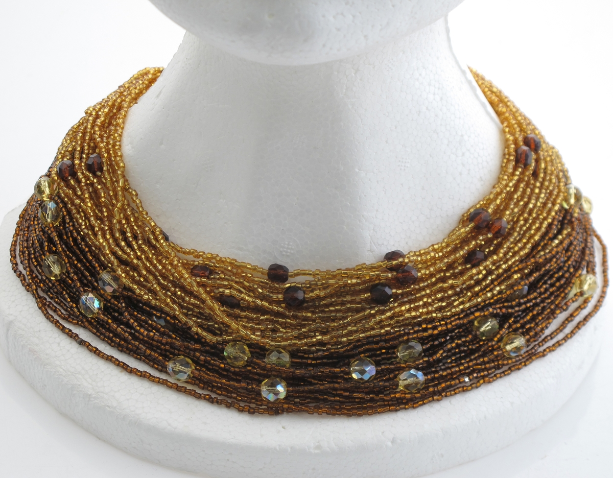 """Perlekjede av brune og gule perler, tredd på 46 lenker, fordelt i 4 """"bunter"""", festet til et metallbeslag, som igjen har montert et kort kjede med, krok og øye."""