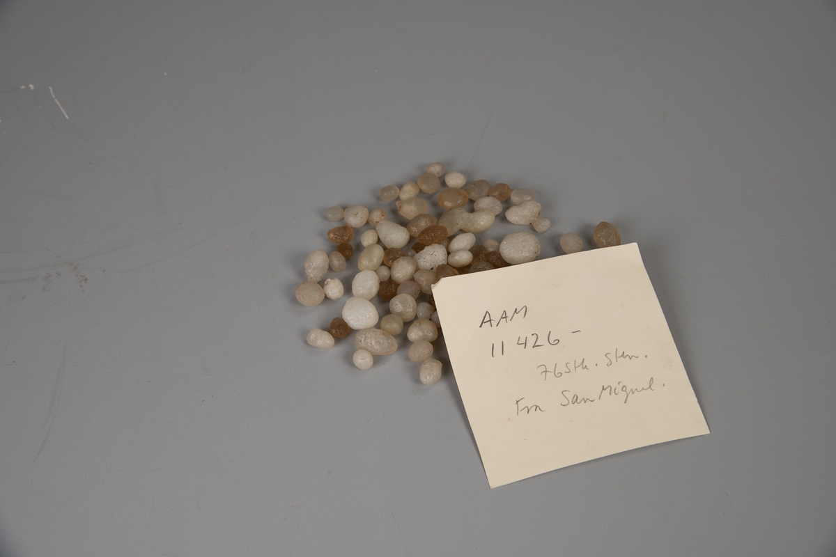 61 små hvite, glattskurte stener, de fleste  som perler. Noen litt større steiner og 15 av  samme sort, men svakt brunlige.