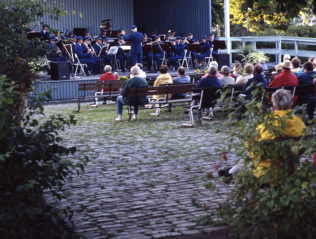 Arboga Blåsorkester spelar på sommaravslutningen i Olof Ahllöfs park. Håkan Harrysson är dirigent. Publiken sitter på bänkar framför scenen.