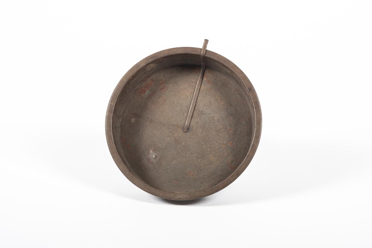 Rund kakeform med flat metallstang. Metallstangen er naglet til midten av formen for å kunne dra den rundt og løsne kaka fra formen.