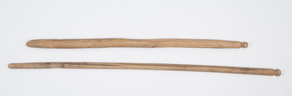 Et par stokker til tresking av korn. Runde med utskåret knapp i enden. Skåret ut i 2 deler, som er festet sammen med lær og hamp.