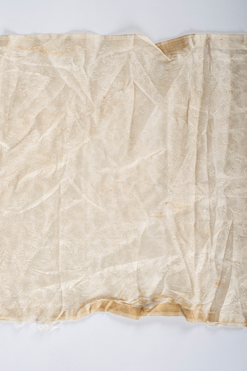 Rektangulært sjal i tynt og glatt tekstil. Blomstermotiv i vevnaden.