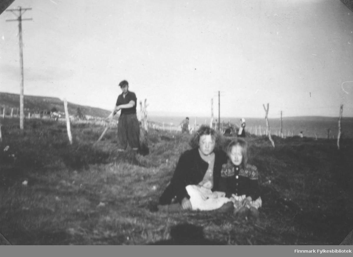 Flere personer fotografert på et jorde i Karlebotn i Nesseby. Sigrid Margit Mathisen (til venstre) og Anna Agnethe Matisen sitter på bakken foran i bildet. Mannen i bakgrunnen er ukjent.