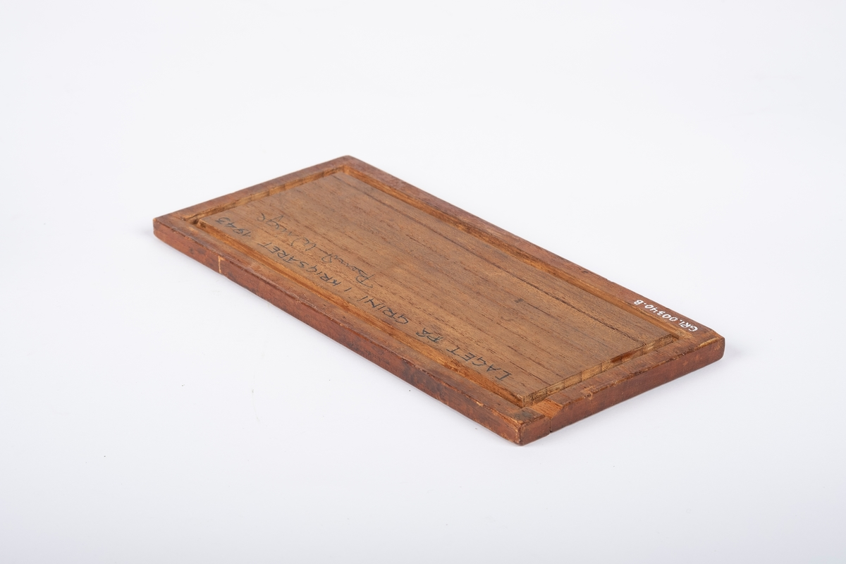 Lokk til treskrin i mørkt tremateriale. Den er dekorert med innfelt metall (marketeri), som består av border og navn langs kanten. Lokket er overflatebehandlet på utsiden.